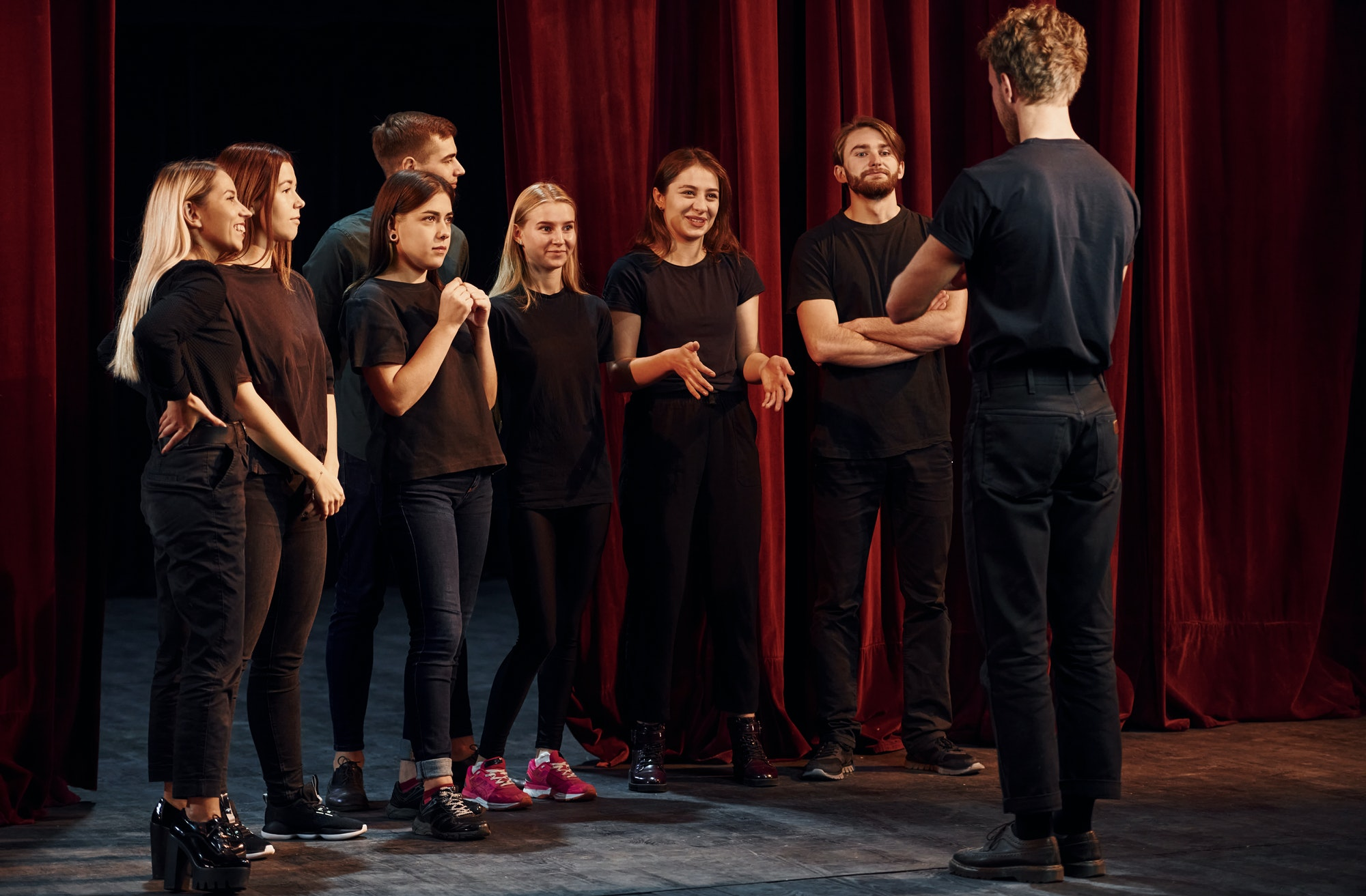 Group of actors in dark colored clothes on rehearsal in the theater